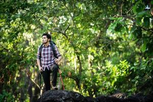 jeune randonneur se reposant au sommet d'une montagne, profitant de la nature et de l'aventure. photo