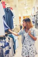 heureuse jeune femme regardant la vente de vêtements dans la boutique. photo