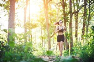 jeune femme jogging sur route rurale dans la nature verte de la forêt. photo