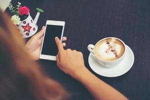 gros plan de femme mains SMS avec son mobile au café. photo