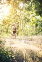 jeune femme jogging sur route rurale dans la nature forestière. photo