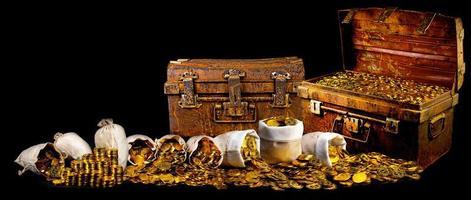 empiler beaucoup de pièces d'or dans un coffre au trésor ancien sur fond noir photo