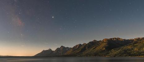 L'aube se lève sur le ciel étoilé et la chaîne des tétons photo