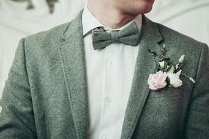 un marié en costume gris et chemise blanche se préparant à l'événement photo