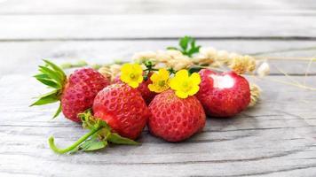 gros plan de fraise avec des brins jaunes secs de carex photo
