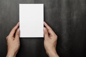 main tenant une maquette de carte d'invitation, modèle de carte de voeux vierge. photo