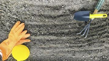 les outils de jardinage reposent sur le sol déterré. préparer le sol photo