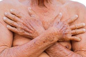 Gros plan sur la poitrine de l'homme senior asiatique avec la texture de deux mains brunes rides photo