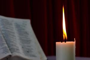 bible ouverte sur une table avec bougie photo