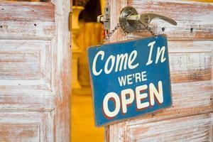 entrez nous sommes ouverts sur la porte en bois ouverte. photo