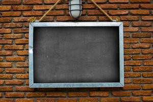 panneau d'affichage vierge accroché sur un mur de briques extérieur de bâtiments photo