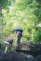 femme de randonneur obtenant de l'aide lors d'une randonnée souriante heureuse de surmonter l'obstacle. photo
