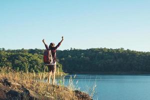 jeune femme randonneur bras ouverts au sommet de la montagne, en dessous d'elle se trouve un grand lac. photo