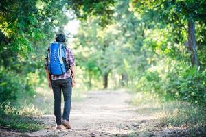 jeune homme hipster marchant sur la route rurale lors de randonnées en vacances. photo
