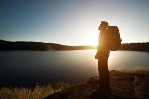 silhouette d'homme randonneur avec sac à dos en montagne paysage coucher de soleil. photo