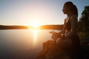 jeune femme en bonne santé pratique le yoga au lac de montagne pendant le coucher du soleil. photo