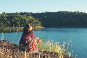 jeune randonneuse assise au sommet de la montagne, en dessous d'elle se trouve un grand lac. photo