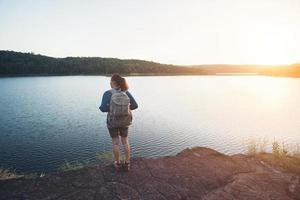 jeune randonneuse debout sur le rocher et profitant du coucher de soleil sur le lac. photo