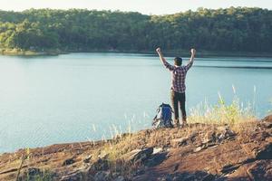heureux randonneur homme touristes avec profiter au sommet d'une montagne. photo