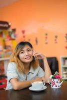 belle jeune femme parlant au téléphone au café a l'air si heureuse. photo