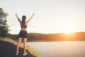 jeune femme de remise en forme réaliser une randonnée au sommet avec le coucher du soleil sur le lac. photo