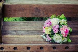 bouquet de mariage sur le fond est un banc en bois photo