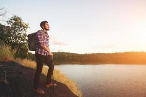 randonneur hipster homme debout sur le rocher et profitant du coucher de soleil sur le lac. photo