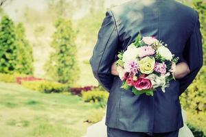 mariée étreinte marié et ses mains tenant le bouquet dans la fête de mariage. photo