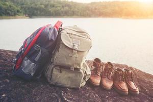 sacs à dos et chaussures avec fond de lac nature. photo