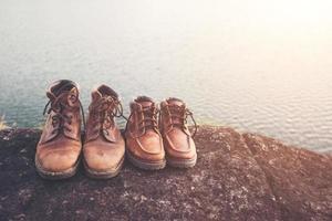 quelques bottes de randonnée sur rocher avec fond de lac nature. photo