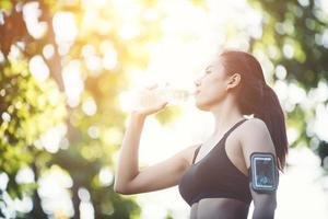 jeune femme faisant une pause pendant la course. eau potable de la bouteille. photo