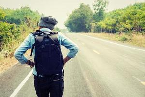 Jeune femme faisant de l'auto-stop portant un sac à dos assis sur la route photo