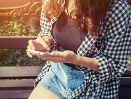 jeune femme tenant un téléphone portable jouant assis dans le parc. photo