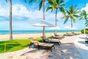belle plage tropicale et mer avec parasol et chaise photo