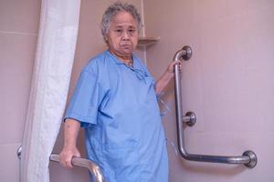 Une patiente asiatique âgée ou âgée utilise la sécurité de la poignée de la salle de bain des toilettes dans la salle d'hôpital de soins infirmiers, concept médical solide et sain. photo
