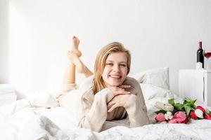 femme allongée sur le lit en pyjama tenant un bouquet de fleurs de tulipes photo