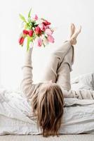 Femme en pyjama tenant un bouquet de fleurs de tulipes lumineuses photo