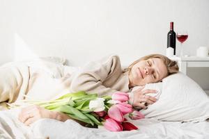 Femme allongée dans le lit en pyjama tenant un bouquet de fleurs de tulipes photo