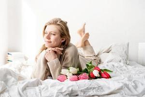 femme heureuse allongée sur le lit tenant un bouquet de fleurs de tulipe photo