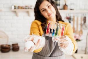 femme tenant des tubes avec des liquides colorés et des œufs blancs photo