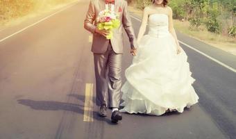 le marié et la mariée marchant sur la route vont se marier photo