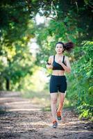 jeune femme de remise en forme qui court sur une route rurale. femme sportive en cours d'exécution. photo