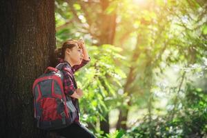 une randonneuse fatiguée se détend avec un grand sac à dos à pied dans la forêt. photo