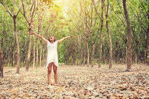 belle jeune femme a levé les bras en profitant de l'air frais dans la forêt. photo