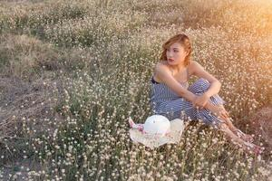 sexy belle femme assise dans un champ de fleurs tristement et solitude photo