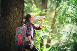 femme une pause en buvant une bouteille d'eau lors d'une randonnée en forêt. photo