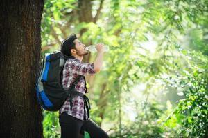 jeune homme assoiffé et boire de l'eau pendant le trek derrière un grand arbre. photo