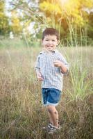 heureux petit garçon asiatique jouant à l'extérieur. garçon asiatique mignon sur le terrain. photo