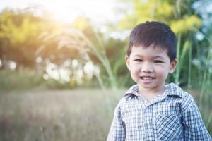 gros plan d'un garçon asiatique mignon jouant et souriant à l'extérieur. photo