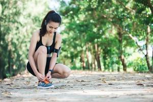 jeune belle écoutant de la musique et attachant des lacets sur sa chaussure. photo
